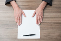 Businesswoman's hands on the desk with the blank paper. Legal contract negotiation. Stock Images
