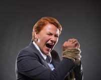 Businesswoman's hands tied up with rope. Businesswoman with red hair big screaming inphoto studio. Lady in business suit having her hands tied up with strong Stock Images
