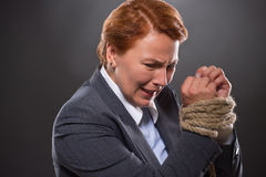 Businesswoman's hands tied up with rope Stock Photo