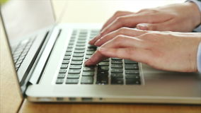 Businesswoman's hands typing on laptop keyboard at desk. Tilt up video close-up of businesswoman's hands typing on laptop keyboard. Executive is sitting at stock footage