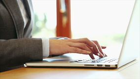 Businesswoman's hands typing on laptop keyboard at desk. Tilt up video of businesswoman's hands typing on laptop keyboard. Executive is sitting at wooden desk stock video