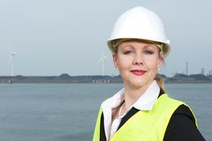 Businesswoman in safety vest and hardhat standing outdoors Royalty Free Stock Photo