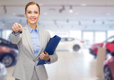 Businesswoman or saleswoman giving car key Royalty Free Stock Photography