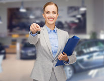 Businesswoman or saleswoman giving car key Royalty Free Stock Photos