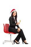 Businesswoman with Santa hat drinking wine Stock Photo