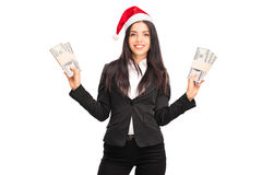 Businesswoman with Santa hat holding money Stock Image