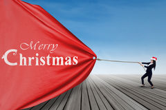 Businesswoman in santa hat pulling christmas banner Royalty Free Stock Photography