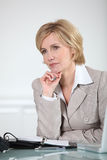 Businesswoman sat at desk Stock Image