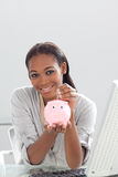 Businesswoman saving money in a piggy-bank Royalty Free Stock Image