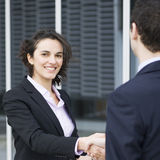 Handshake between businesspeople. Businesswoman saying hello to candidate and smiling into the camera royalty free stock image