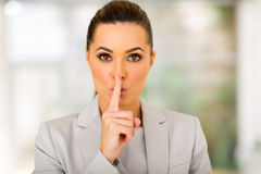 Businesswoman saying shhh. Pretty young businesswoman saying shhh Royalty Free Stock Photography