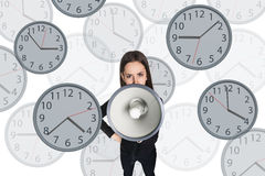 Businesswoman scream to megaphone among clocks. Royalty Free Stock Photo