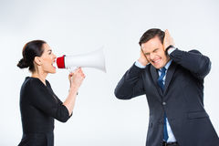 Businesswoman screaming at businessman. Young businesswoman screaming in megaphone at businessman on white Royalty Free Stock Photography
