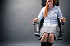 Businesswoman Screaming for Help. A young businesswoman tied to an office chair screaming for help Royalty Free Stock Image