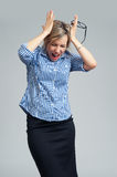 Businesswoman screaming and holding head in hands Stock Photos