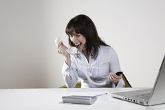 Businesswoman Screaming Into Phone Receiver. Angry young businesswoman screaming into phone receiver at desk Royalty Free Stock Images