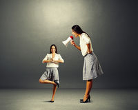Businesswoman screaming at small yoga woman Royalty Free Stock Photos