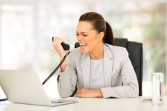 Businesswoman screaming telephone. Angry young businesswoman screaming at telephone in office Royalty Free Stock Photo