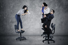Businesswoman screaming to her teamwork. Picture of young businesswoman screaming to her teamwork with a megaphone while standing on the chair Royalty Free Stock Image