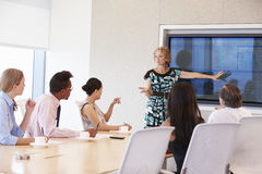 Businesswoman By Screen Addressing Boardroom Meeting Stock Photos