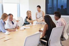 Businesswoman By Screen Addressing Boardroom Meeting Stock Image