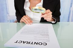 Businesswoman scrutinizing contract with magnifying glass Stock Images