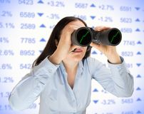 Searching the best financial investment. Businesswoman searching with binoculars the opportunities to invest in stock market. All screen content is designed by stock photos