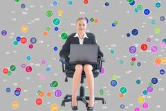 Businesswoman seated with a laptop in front of a digital background royalty free stock photo