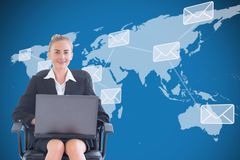 Businesswoman seated with a laptop in front of a digital world map Royalty Free Stock Photo