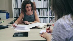 Businesswoman and secretary working with documents in office stock video footage