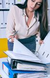 Businesswoman or secretary working with many documents in folders on her desk. Deadlines for the submission of reports. Deadlines for the submission of reports stock photo