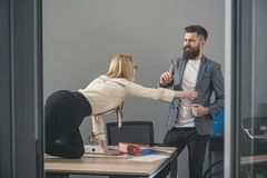 Businesswoman seducing boss man at office table Royalty Free Stock Images