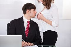 Businesswoman seducing boss in office Royalty Free Stock Image