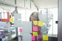 Businesswoman seen through adhesive notes on glass in creative office Royalty Free Stock Images