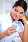 Businesswoman sending message with smartphone sitting in the office Royalty Free Stock Photos