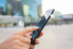 Businesswoman sending messages with her mobile phone, building B Stock Image