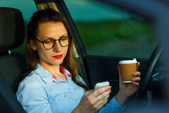 Businesswoman sending a text message and drinking coffee while d Stock Photography