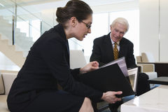 Businesswoman and senior executive in lobby. Royalty Free Stock Image