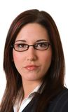 Businesswoman serious headshot. Attractive young woman in glasses and business suit with serious expression looks directly into camera; headshot isolated on Stock Photography