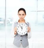 Businesswoman serious, hold clock Stock Image
