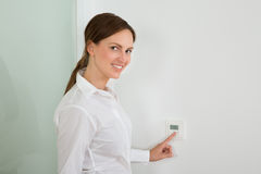 Businesswoman Setting The Temperature On Digital Thermostat Stock Photo