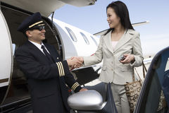 Businesswoman Shaking Hand With Pilot Royalty Free Stock Image