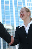 Businesswoman shaking hands. Outside a modern office building Stock Image