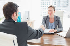 Businesswoman shaking hands with a businessman Stock Images