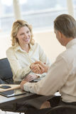 Businesswoman Shaking Hands With Colleague At Desk. Happy mature businesswoman shaking hands with male colleague at office desk Stock Image