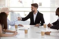 Businesswoman shaking hands with company client at meeting in office. Businesswoman shake hands with company client at meeting in office. Diverse businesspeople royalty free stock photo