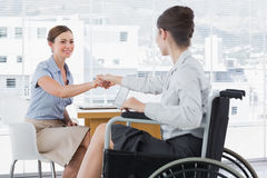 Businesswoman shaking hands with disabled colleague. At desk in office royalty free stock photos