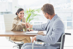 Businesswoman shaking hands with disabled colleague. In an office royalty free stock images