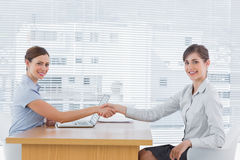 Businesswoman shaking hands with interviewee and both smiling at Stock Photography