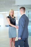 Businesswoman shaking hands in office Stock Photos
